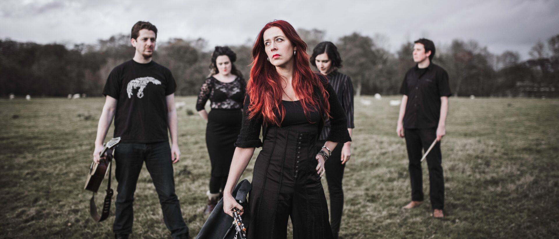 A red-haired woman dressed casually in black and holding the Northumberland pipes poses in a field next to her band mates