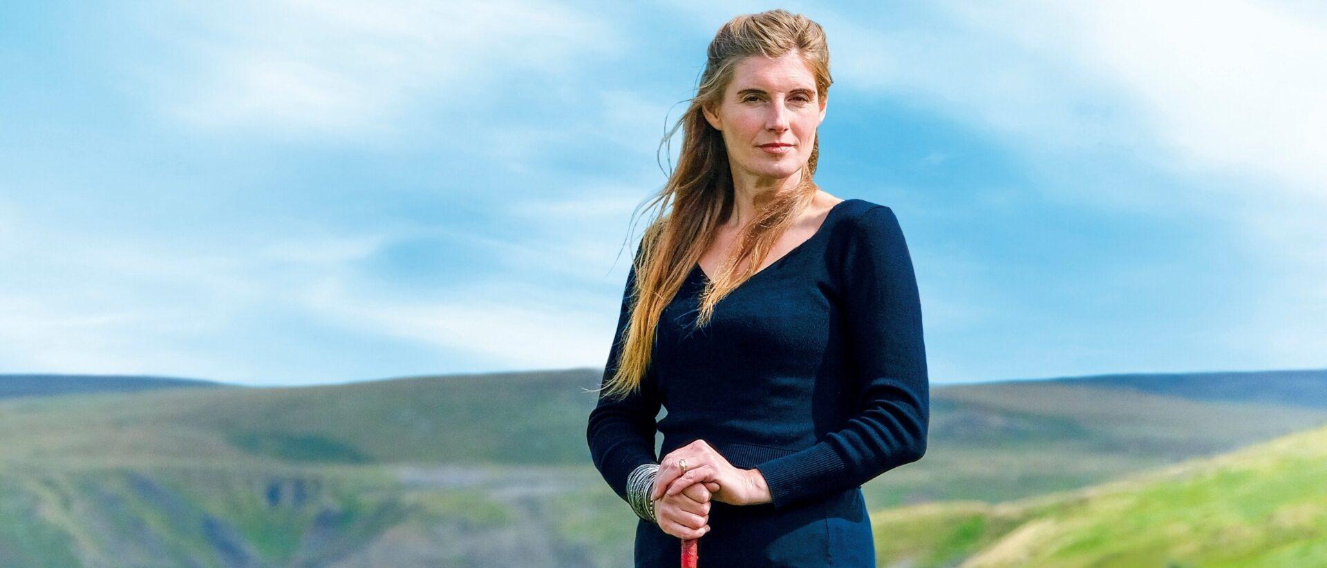 Amanda Owen standing on a hill.