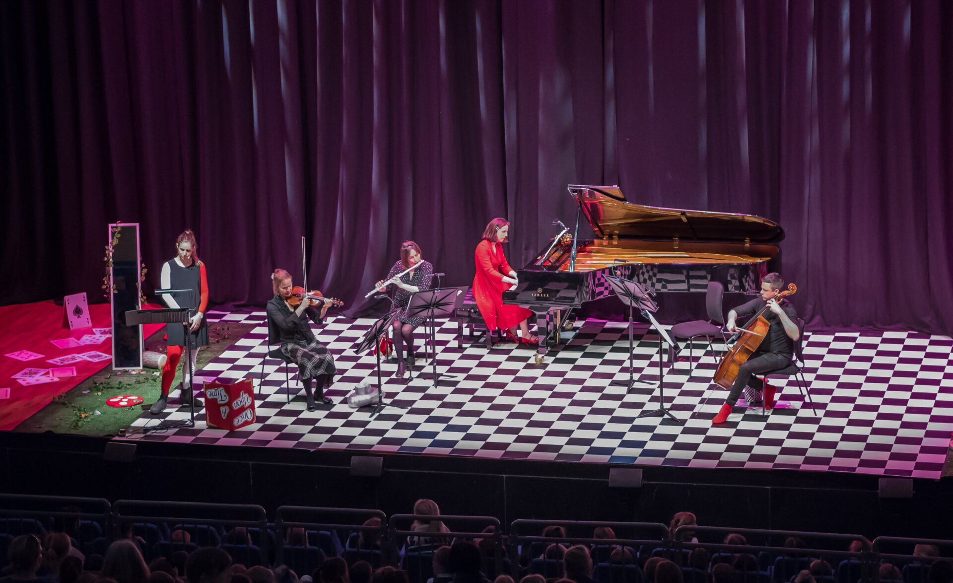 A group of musicians dressed in red and black play on a stage with a chequerboard-patterned floor