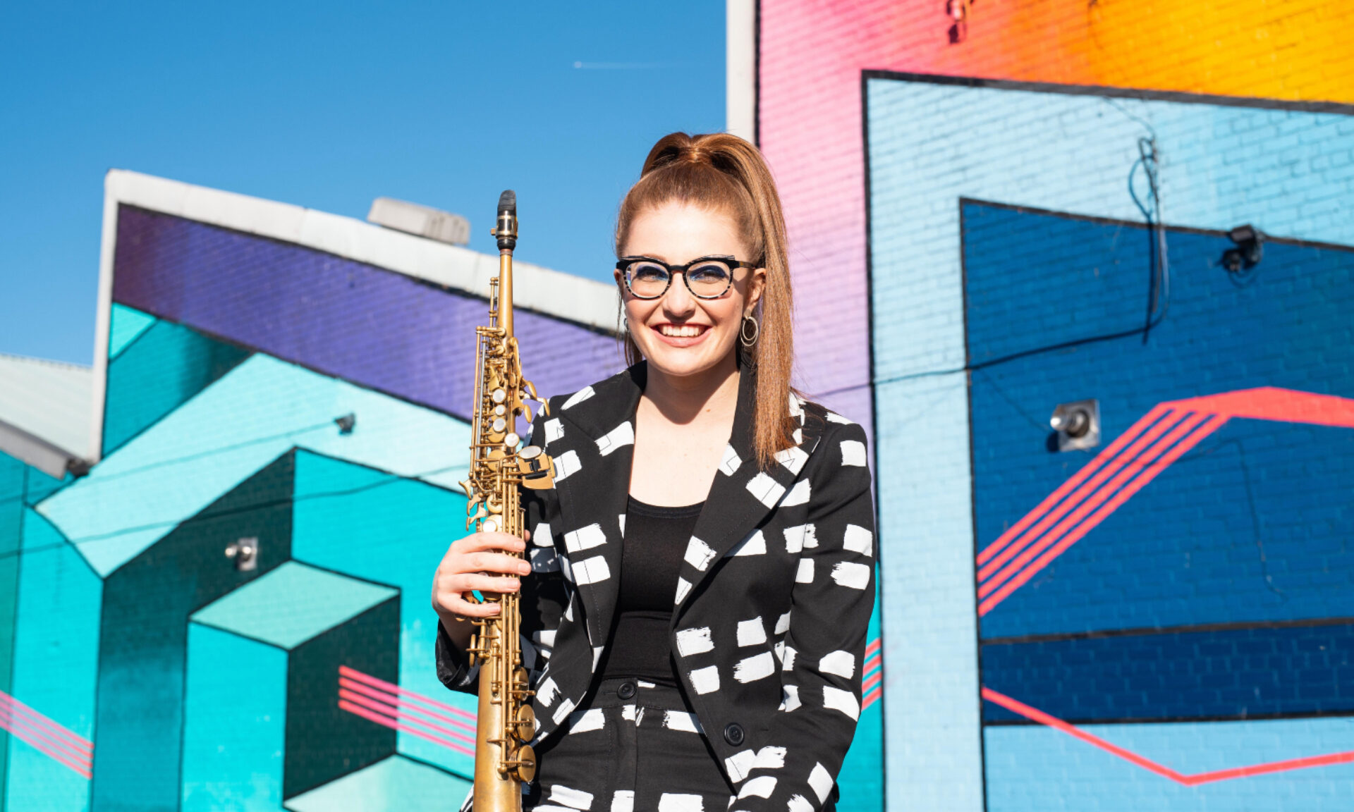 Jess Gillam holds her saxphone wearing a patterned monochrome suit in front of a bright graffiti'd wall
