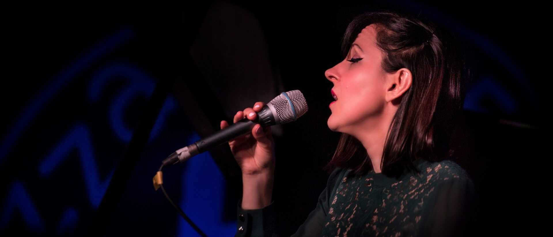 Georgia Mancio sings soulfully into a microphone