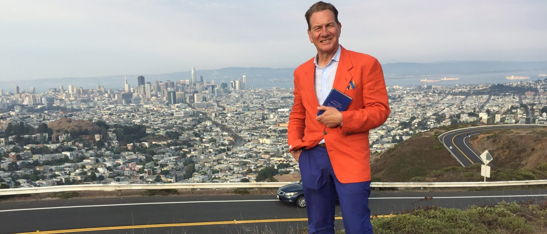 Michael Portillo standing on a hill overlooking a city with a book smiling at the camera.