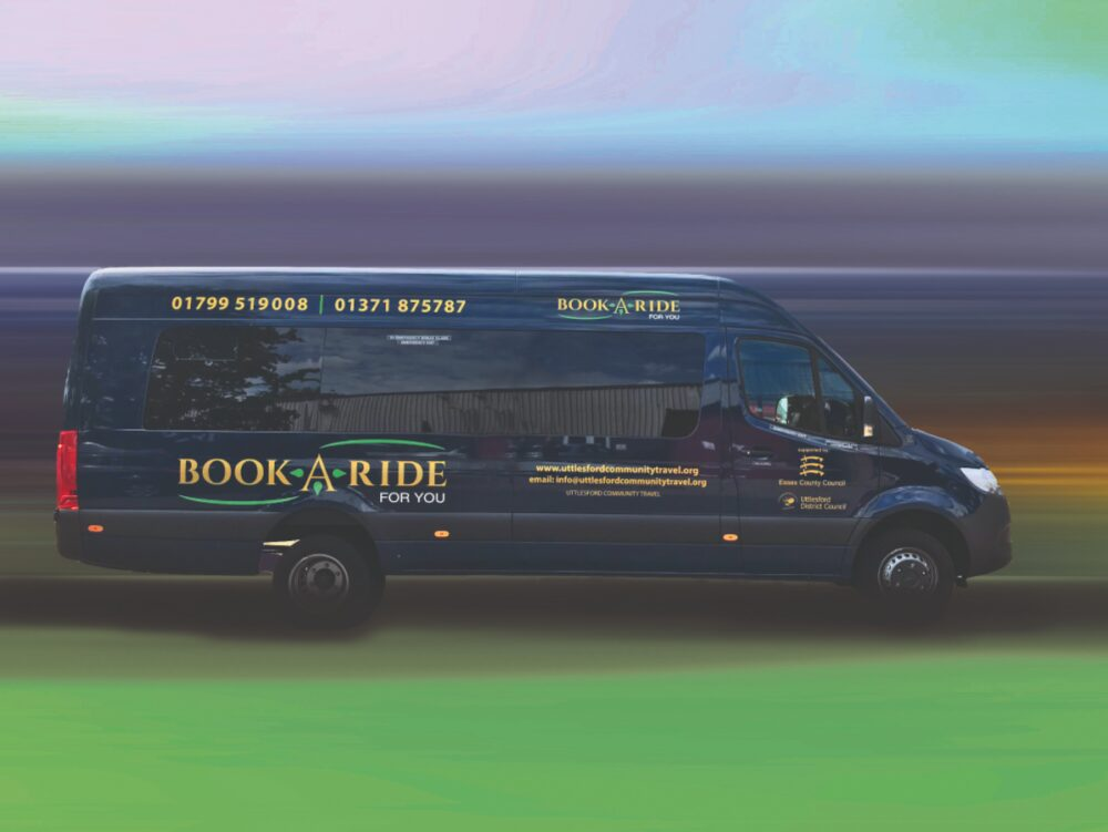 A navy minibus with 'Book a ride' prominently written across the side