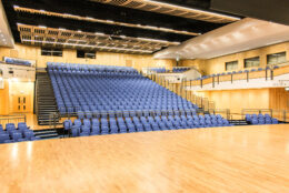 Inside Saffron Hall, a modern auditorium panelled with light wood with a big bank of tiered blue seats