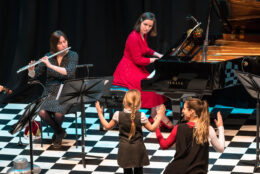 A small child is encouraged to 'conduct' a group of players on a chequerboard patterned stage