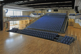 Saffron Hall's light and airy auditorium clad with light-coloured wood with a big band of royal blue theatre seats in the middle