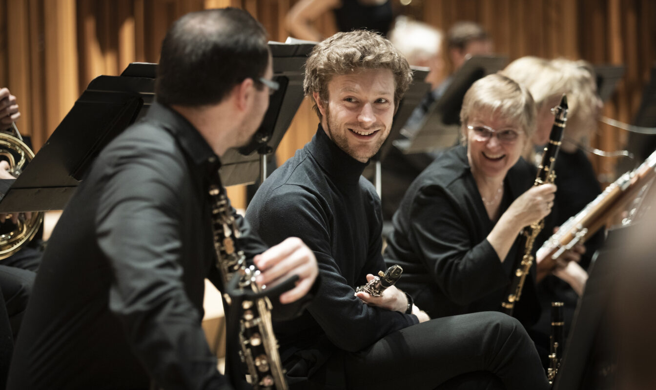 Three smiling Britten Sinfonia players chat mid-rehearsal holding their instruments