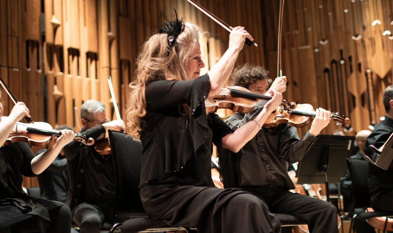 Britten Sinfonia finishing a piece during a concert on stage.