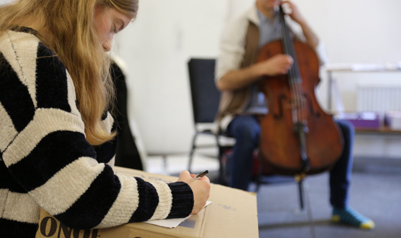 A teenager in the foreground is writing intently while someone in the background plays the cello