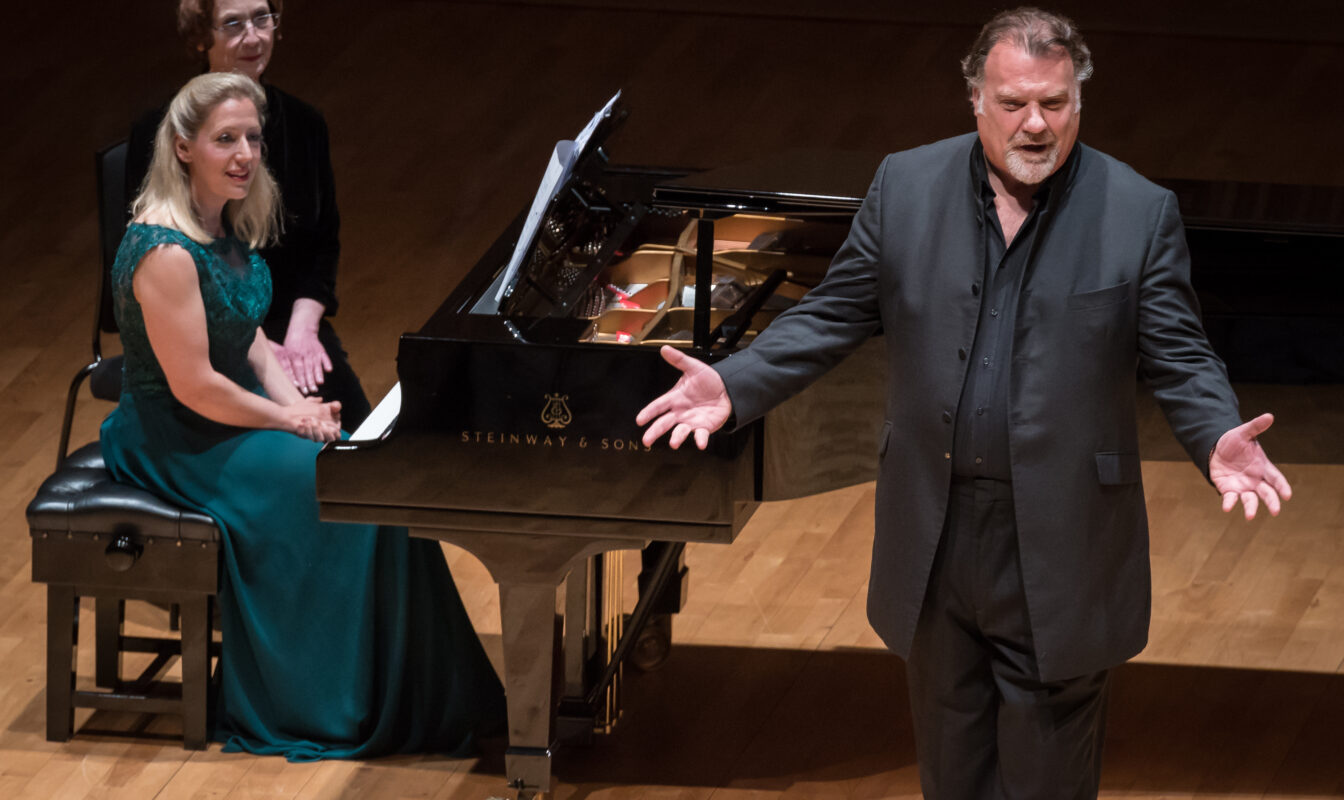 Singer Bryn Terfel gestures playfully at the audience mid-song