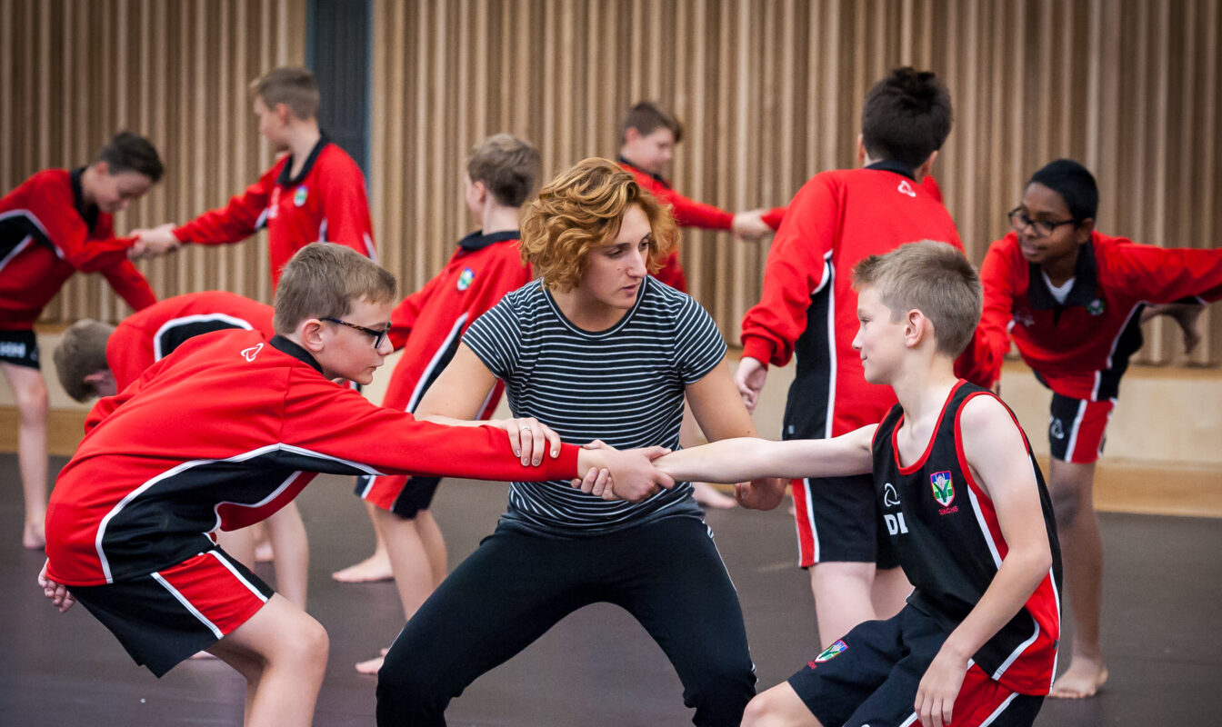 Two teenage boys in PE uniform hold a dance pose guided by a dance instructor