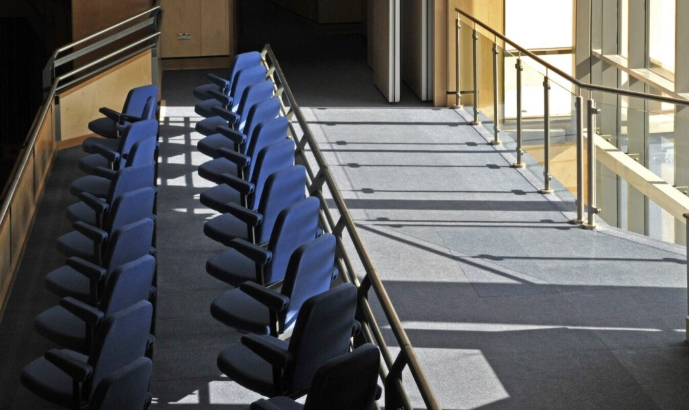 Light floods through the windows of the auditorium on to the blue theatre seats