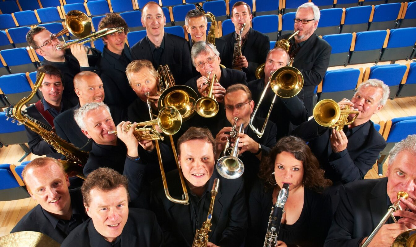 The BBC Big Band looking at the camera during a photoshoot with their instruments.
