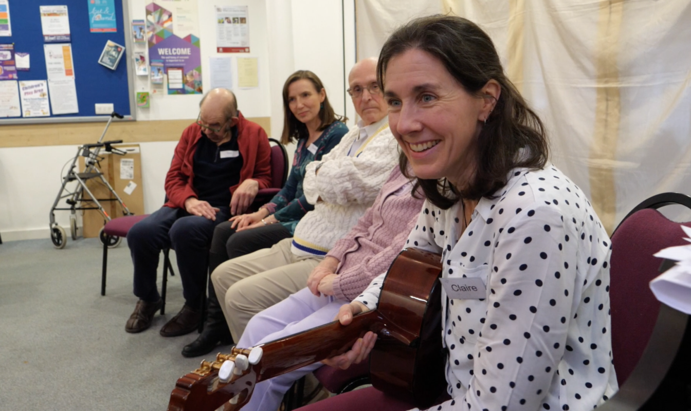 A music therapy group sits making music together, with Claire Molyneux leading them holding a guitar
