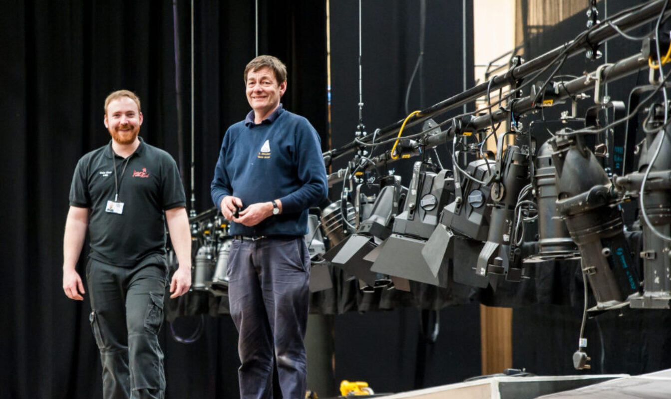 Two men in lanyards pose next to a lowered lighting rig