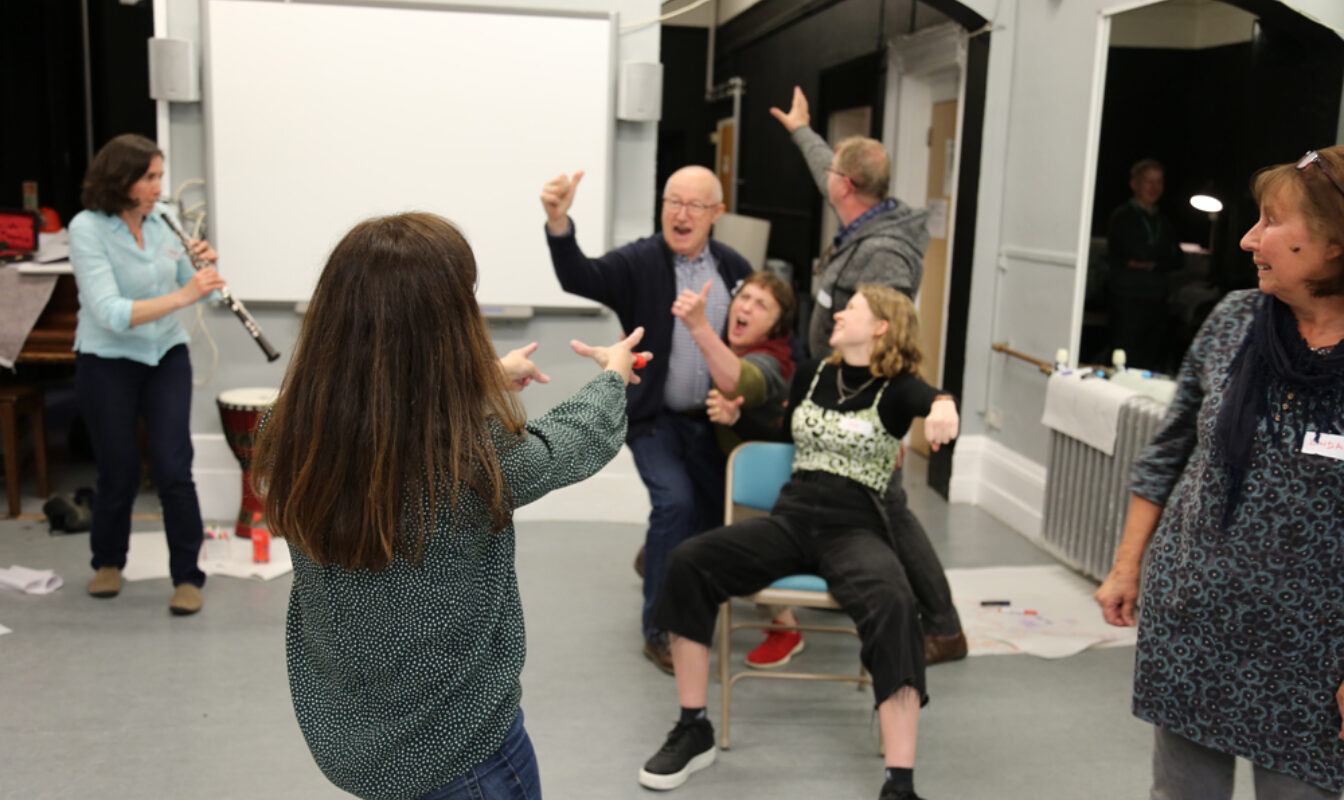 A 'freezeframe' image of participants of all ages making a dramatic tableau while someone plays the clarinet