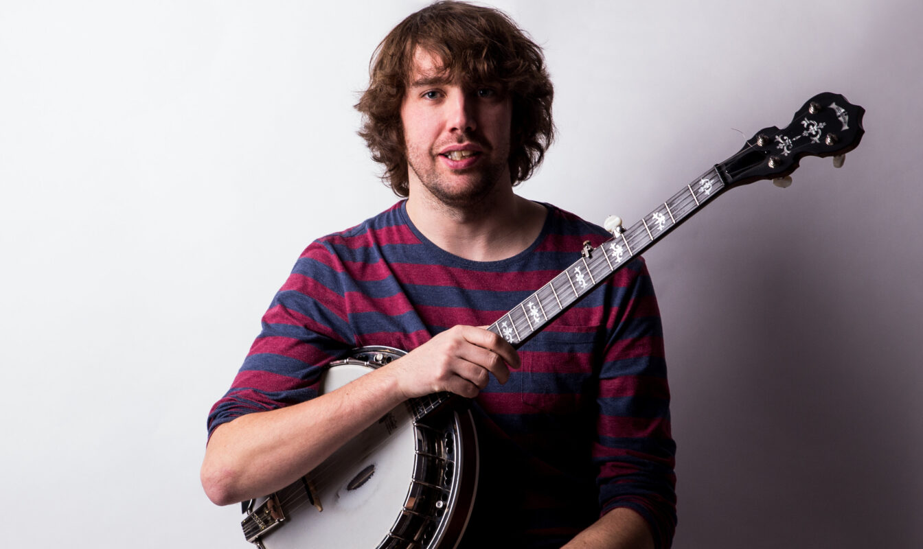 Professional headshot of Dan Walsh holding banjo