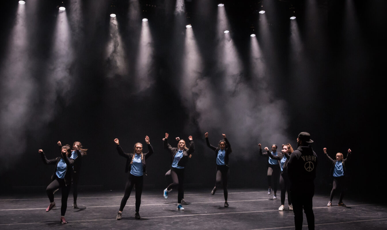 Young dance students in street clothes rehearse on a dramatically lit stage overseen by a coach
