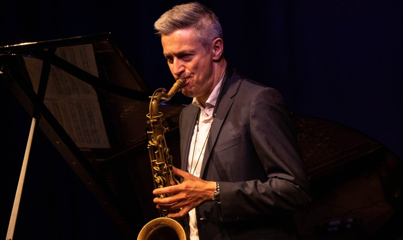 Man with light hair plays saxophone in a darkened room