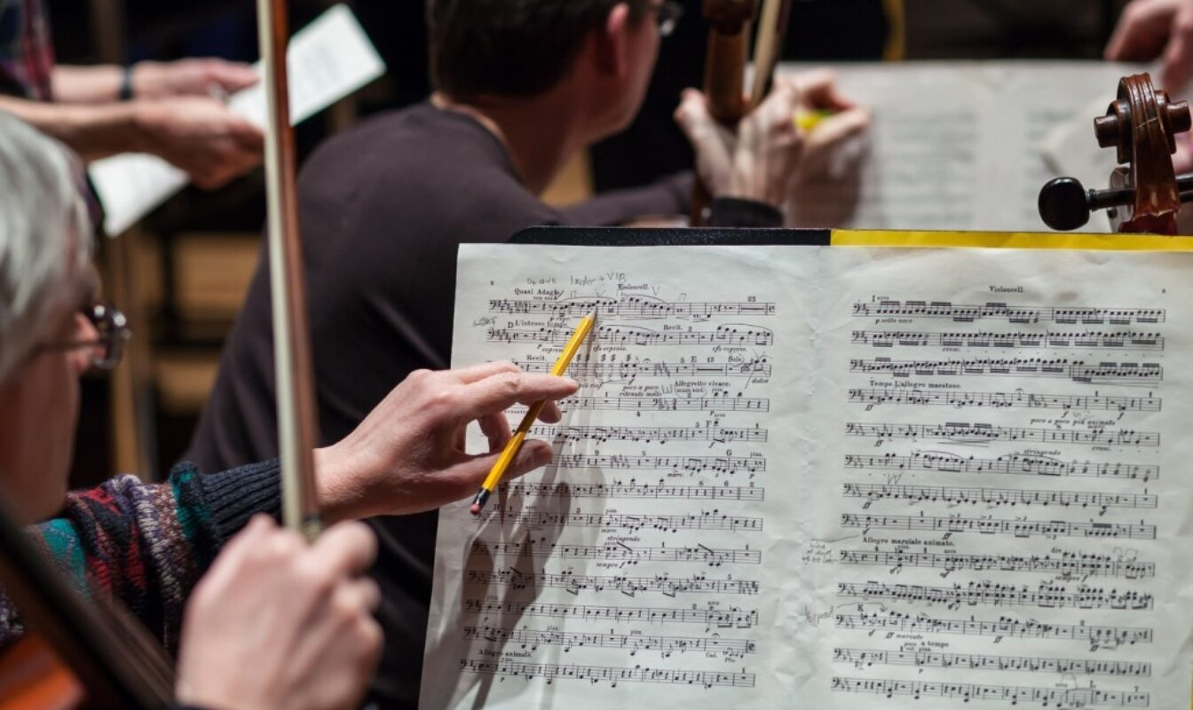 An instrumentalist makes pencil notes on sheet music