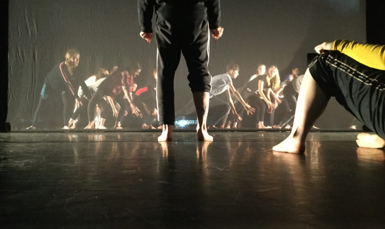 One dancer stands centre-stage, while other dancers make a dynamic tableau behind them through a screen