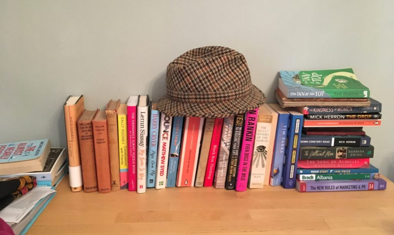 Colourful books stacked on a wooden desk with a tweed trilby hat placed on top