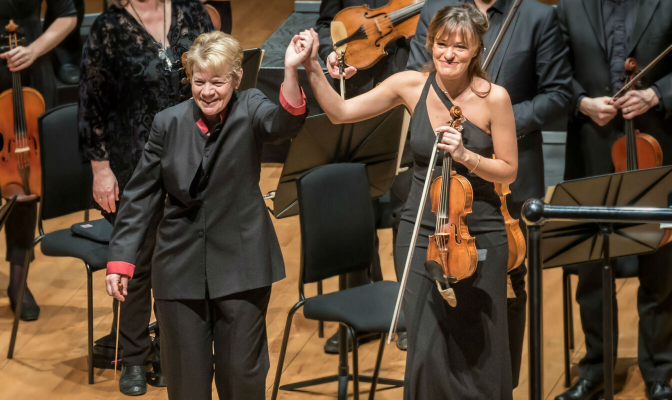 Marin Alsop and Nicola Benedetti hold hands, about to bow, after a performance