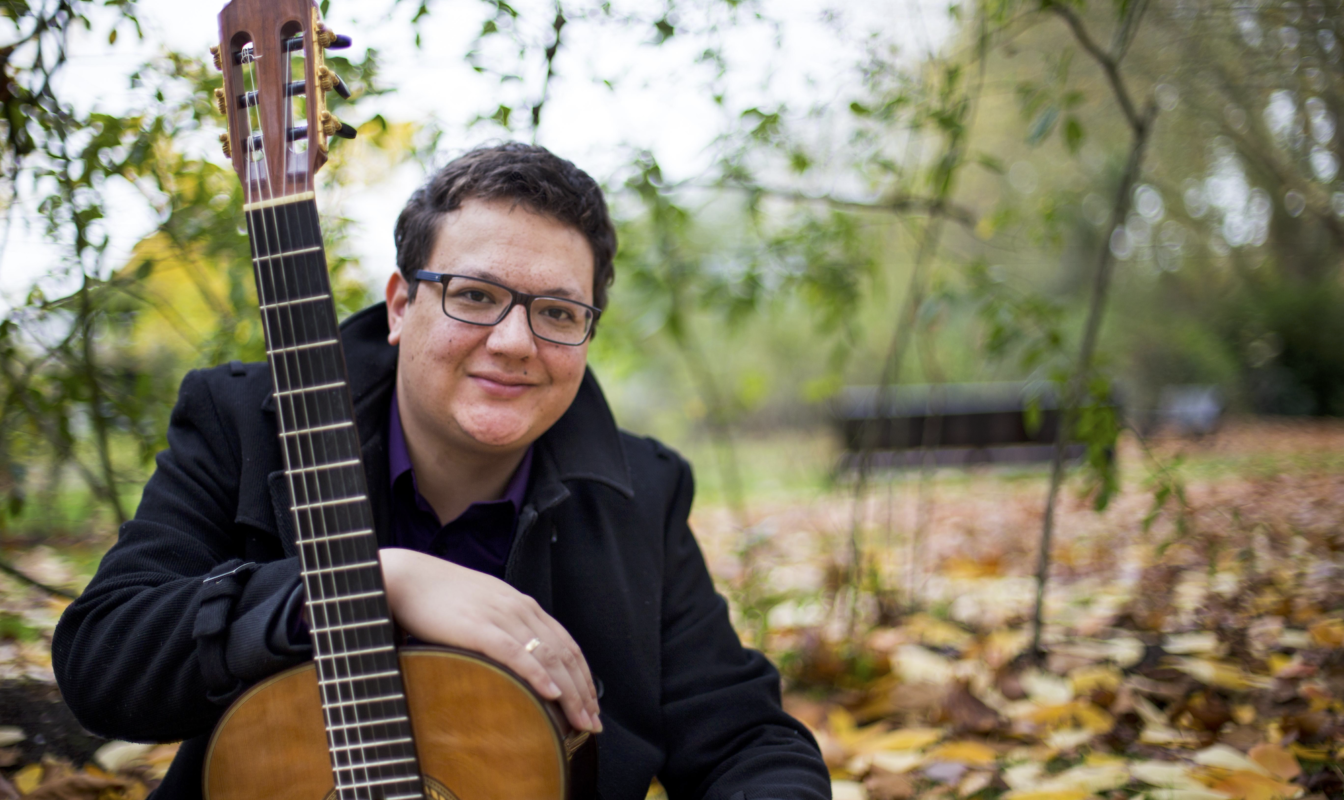 Professional headshot of Michael Butten holding a guitar outside