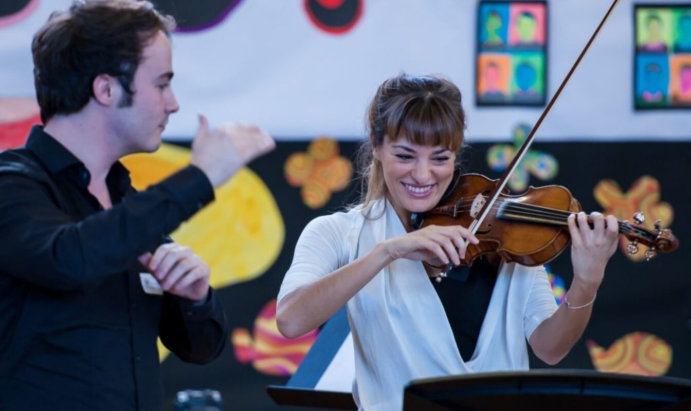 Nicola Benedetti plays violin while Ben Gernon conducts against the backdrop of a primary school assembly hall