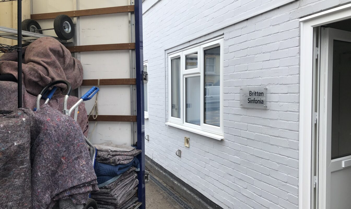 Office furniture is moved into a van from a building with a sign reading 'Britten Sinfonia Office'