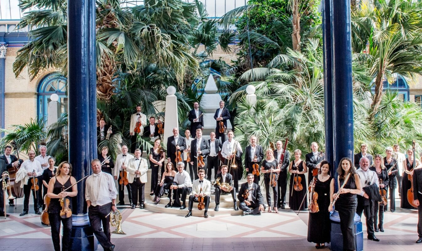 Orchestral players stand posed with their instruments in a lush, plant-filled indoor courtyard with light streaming in from the glass roof above