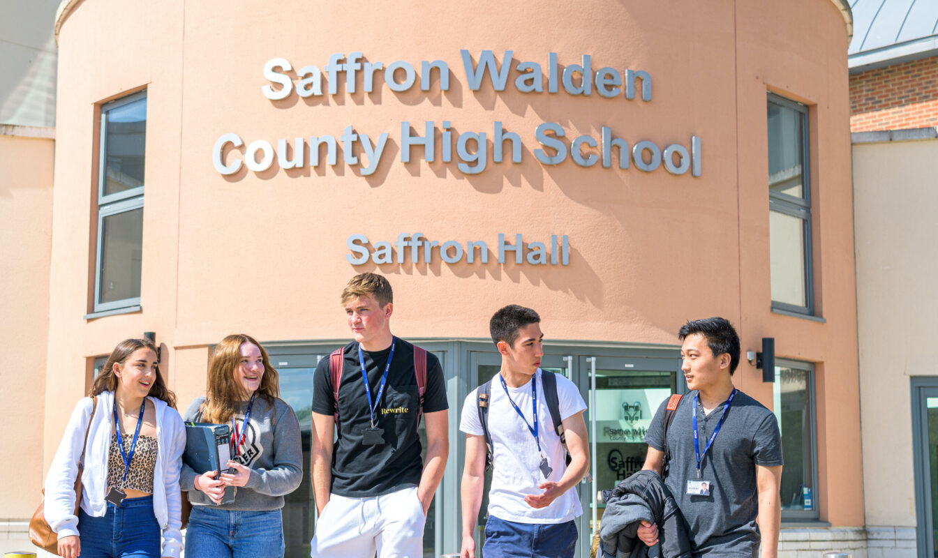 A group of 5 students in casual clothes chat outside the front entrance of Saffron Walden County High School