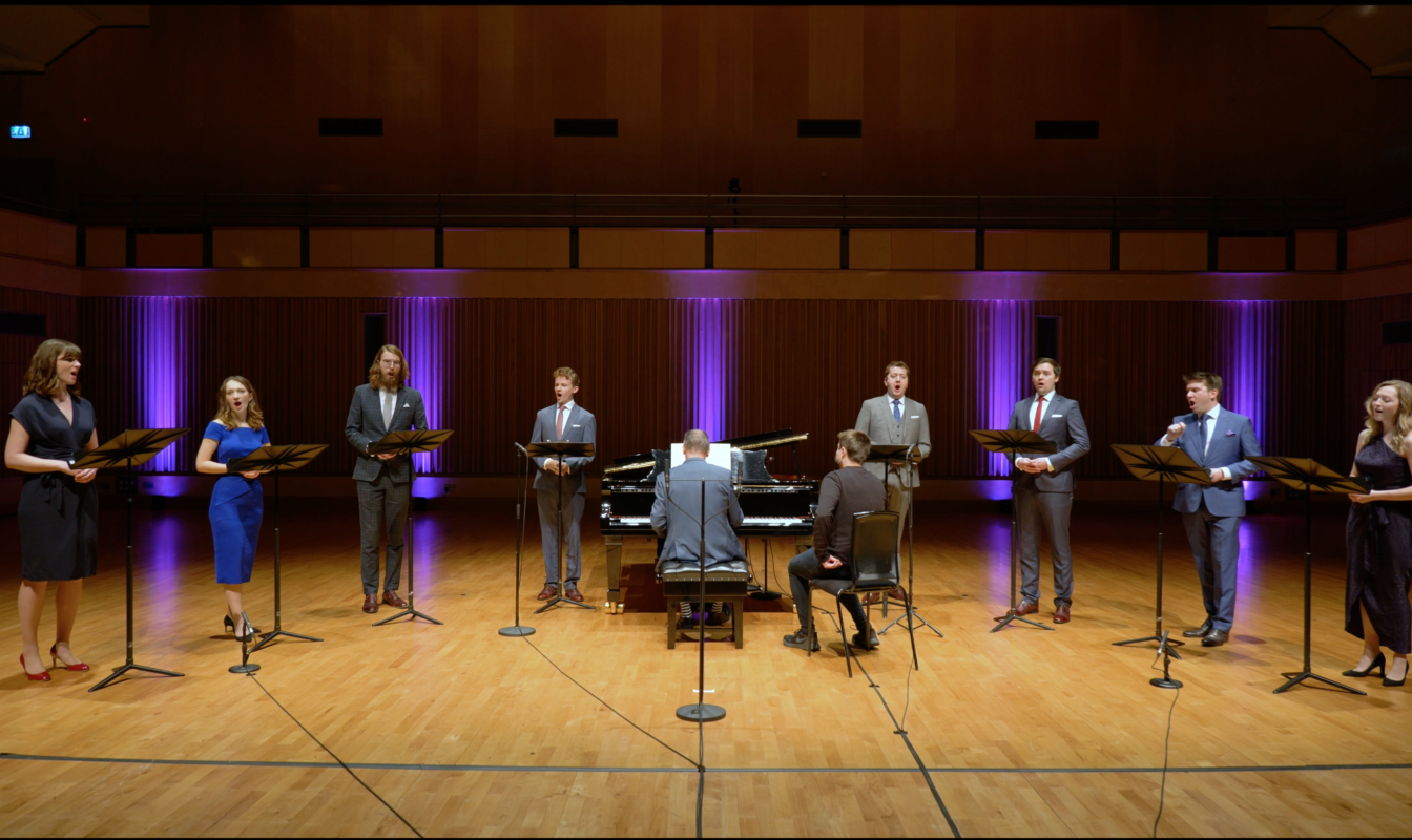 The singers of VOCES8 perform with a pianist on the Saffron Hall stage