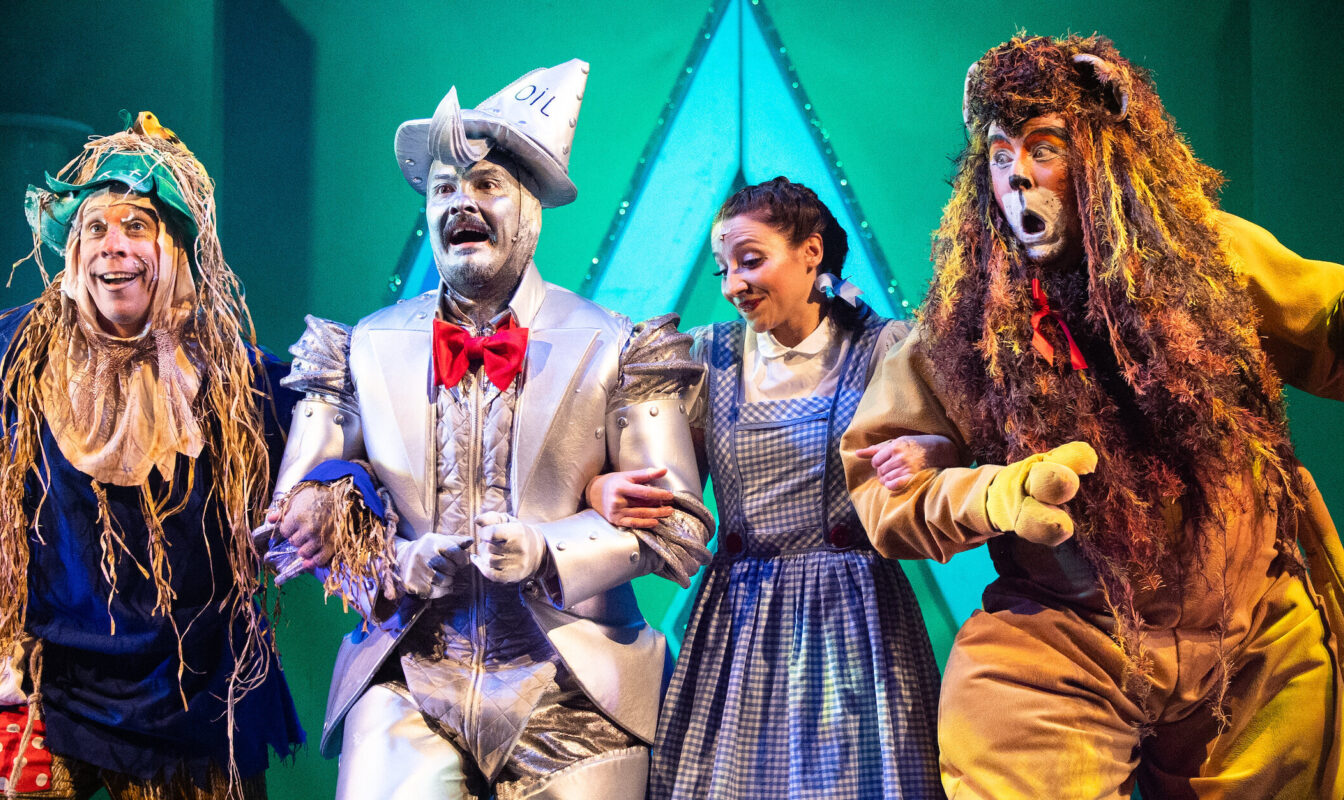 Actors dressed as the main characters from Wizard of Oz link arms on a stage with a emerald green background