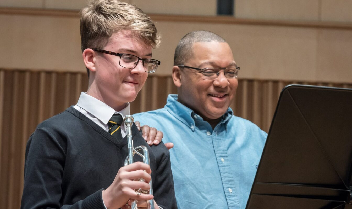 Wynton Marsalis places his hand proudly on the shoulder of a young student holding a trumpet