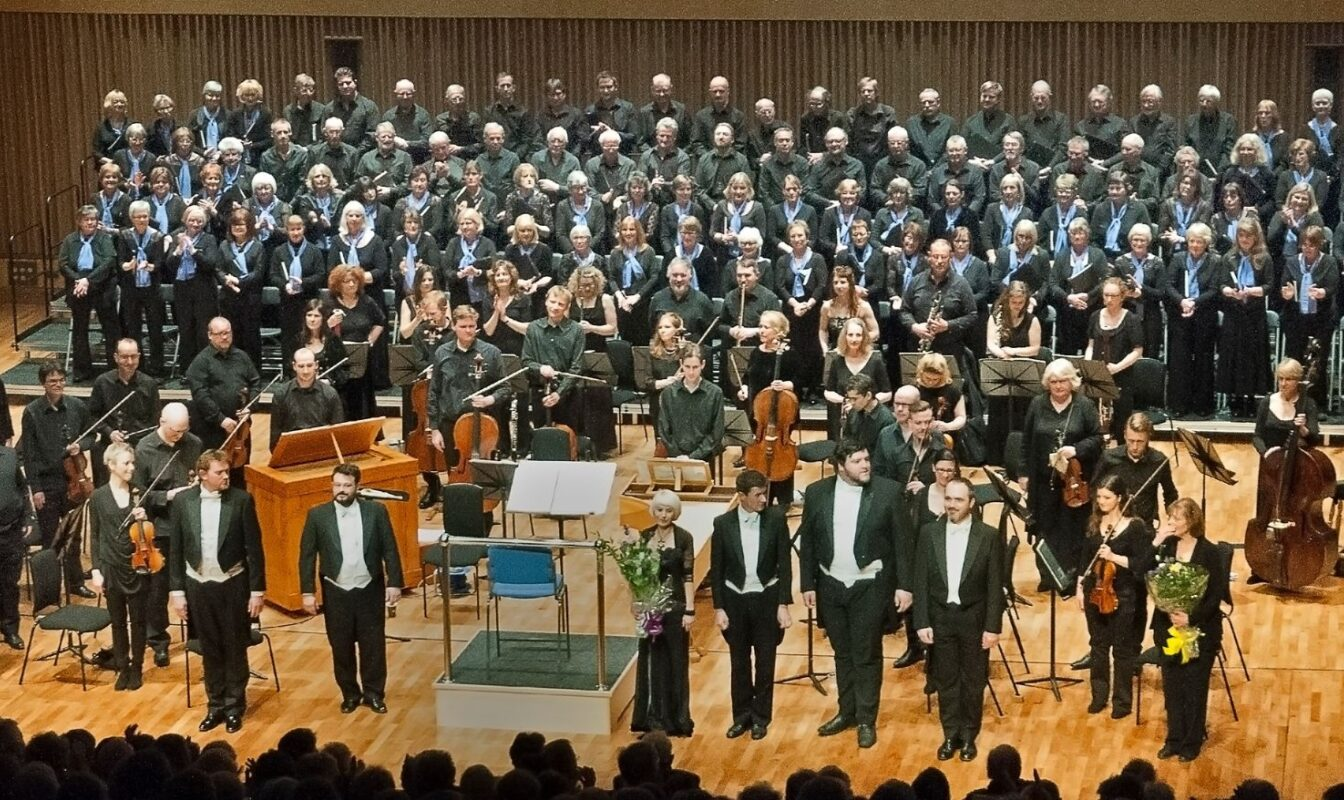A concert stage full of people including a large choir on risers, a chamber orchestra and several formally dressed soloists