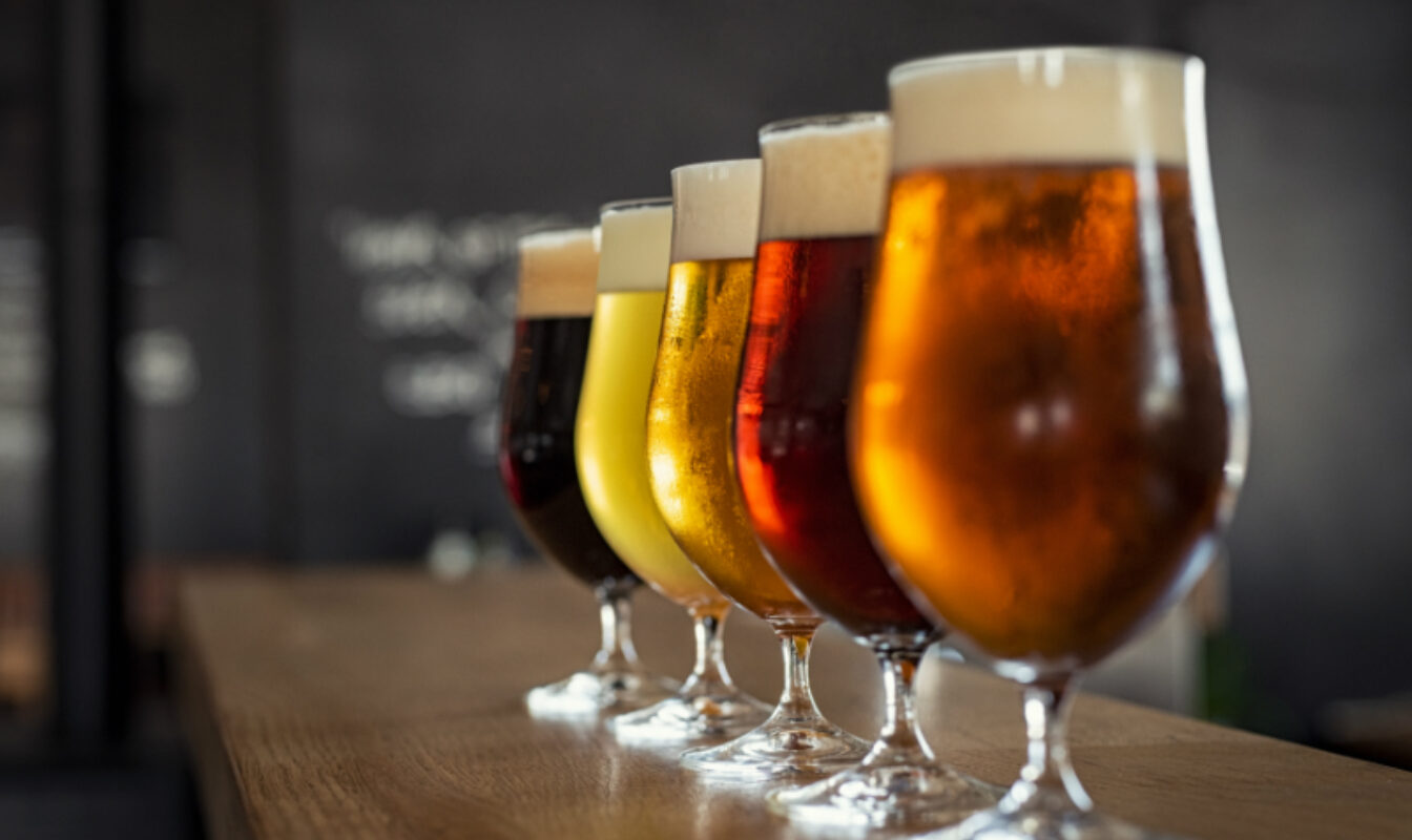 A line-up of different beers in frosted goblets on a bar