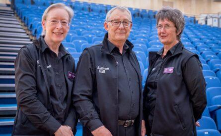 Three smiling volunteers in their stewarding uniforms