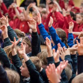 Children in colourful primary school uniforms raise their hands