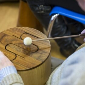 An older person hits a slotted drum with a beater